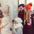 Image of parents window shopping with young girl at Christmas time wearing hats and scarves.