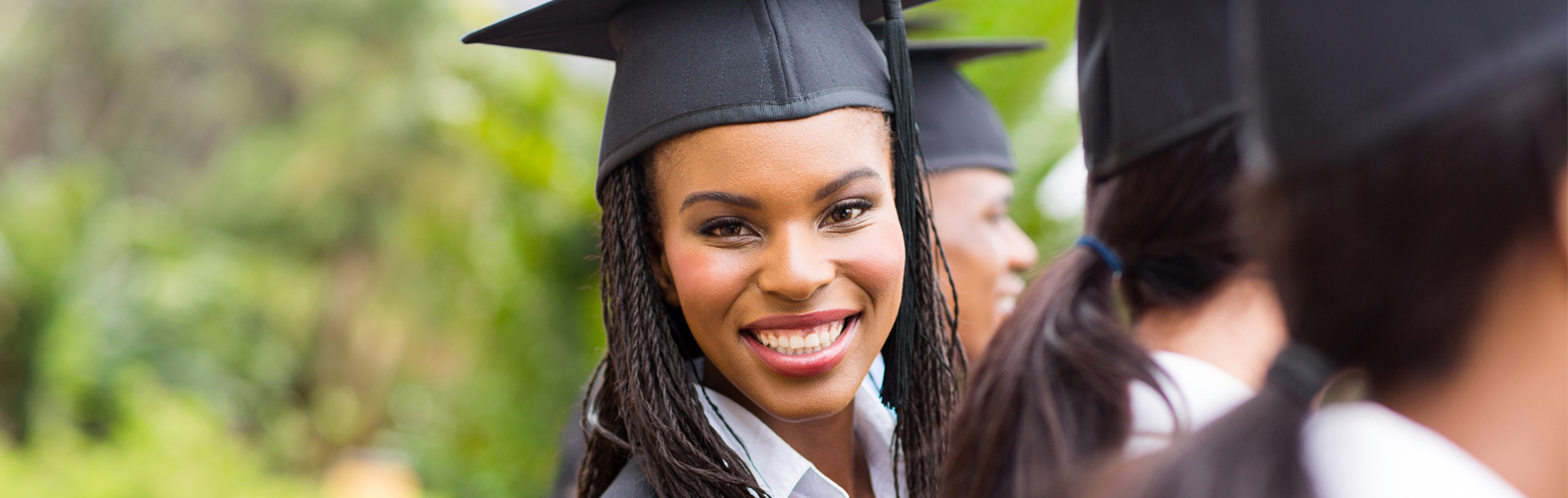 Image of college graduates wearing cap and gown. African American woman turning to face the camera, smiling.