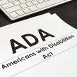 Photo of stack of papers next to keyboard that says ADA Americans with Disabilities Act