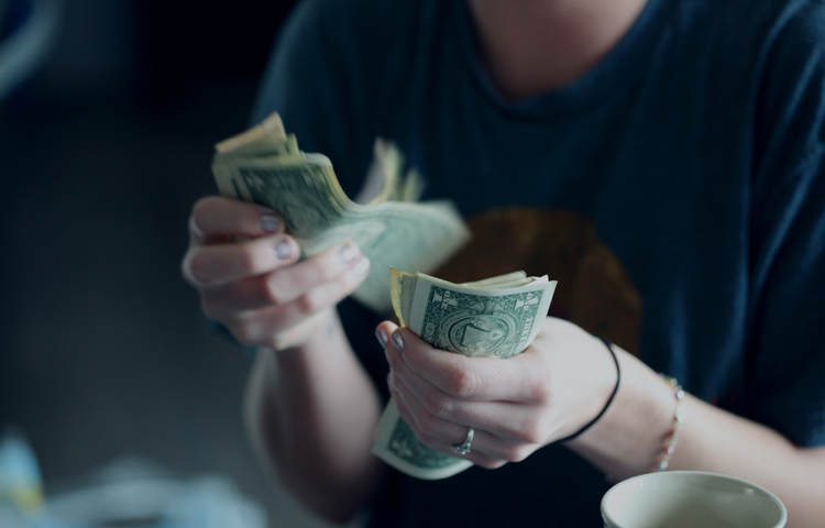 Image of young woman counting dollar bills.